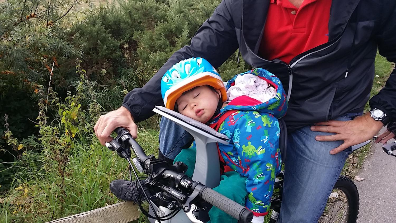 Child asleep on child bike seat