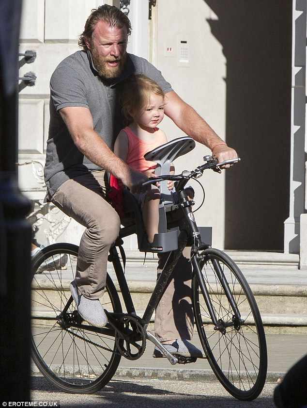 Guy Ritchie on bike with child seat